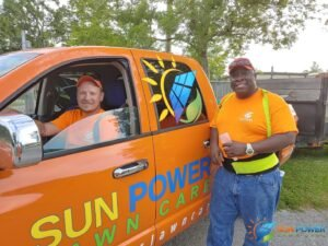 Sam and Kyle pose with the Sun Power lawn Care Truck